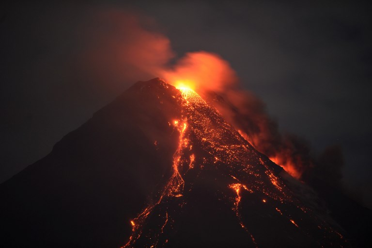 This photo taken on January 28, 2018 shows Mayon volcano spewing lava ash from its crater, as seen in Daraga town, south of Manila in Albay province. Authorities have imposed a no-go zone around the 2,460-metre (8,070-foot) mountain as they warned of a hazardous eruption within days, leaving more than 77,000 people stuck in crowded shelters, likely for months.  / AFP PHOTO / Ted ALJIBE