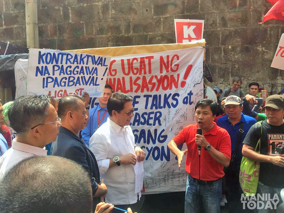 Workers did not allow DOLE Sec. Bello and Usec. Maglunsod to speak in the rally program. Photo by Kathy Yamzon.