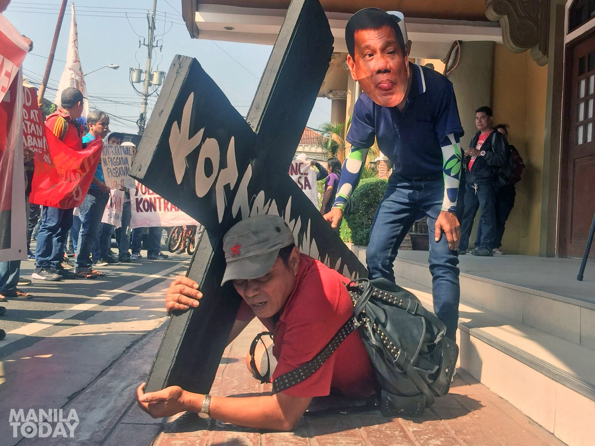 Worker depicted to bear the cross of contractualization. Photo by Kathy Yamzon.